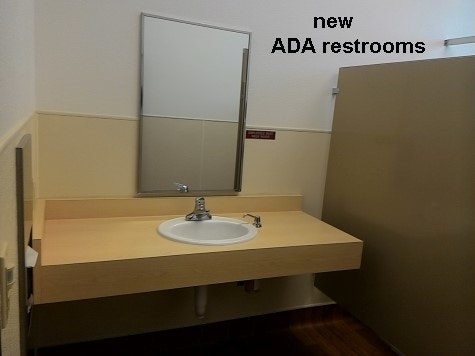 inside updated community building new ADA restroom sink, mirror, stall wall.