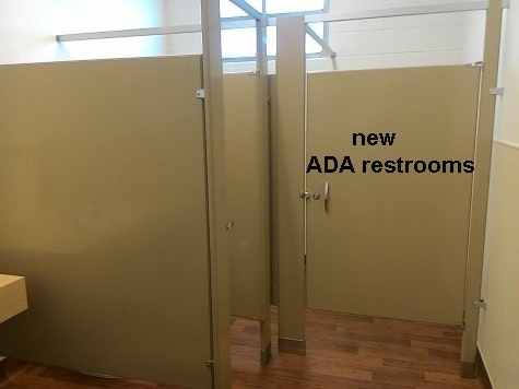inside updated community building new ADA restroom showing stalls walls.