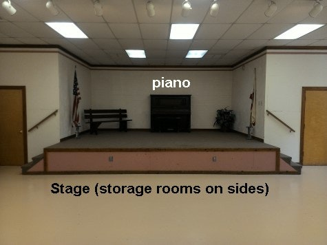 inside updated community building showing new floor to original stage with piano in background.  Storage rooms on each side.
