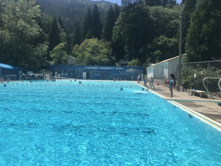 Looking down the length of the swimming pool bath house in far end with trees and mountain beyond that. A few in pool and on deck.