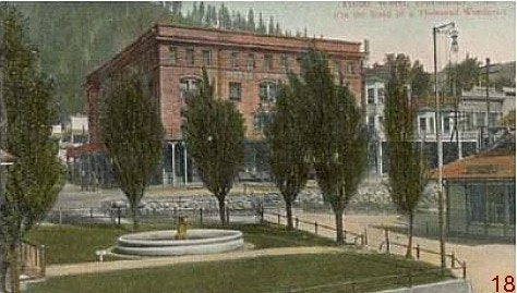 Old picture of Dunsmuir Fountain in foreground and Weed Hotel in background hill with trees behind hotel