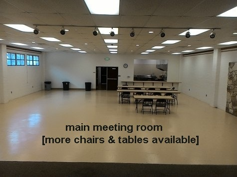 inside updated community building from stage to kitchen. A few tables and chairs for a meeting.
