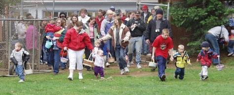 Ball Field on Easter Egg hunt. A few adults and lots of young children with baskets to collect eggs in grass.