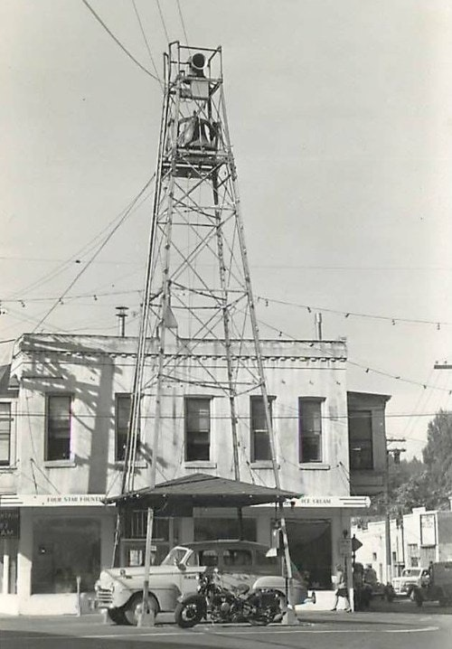 black and white photo containing streets, 1950's police car, motorcycle, bell tower, building in background.
