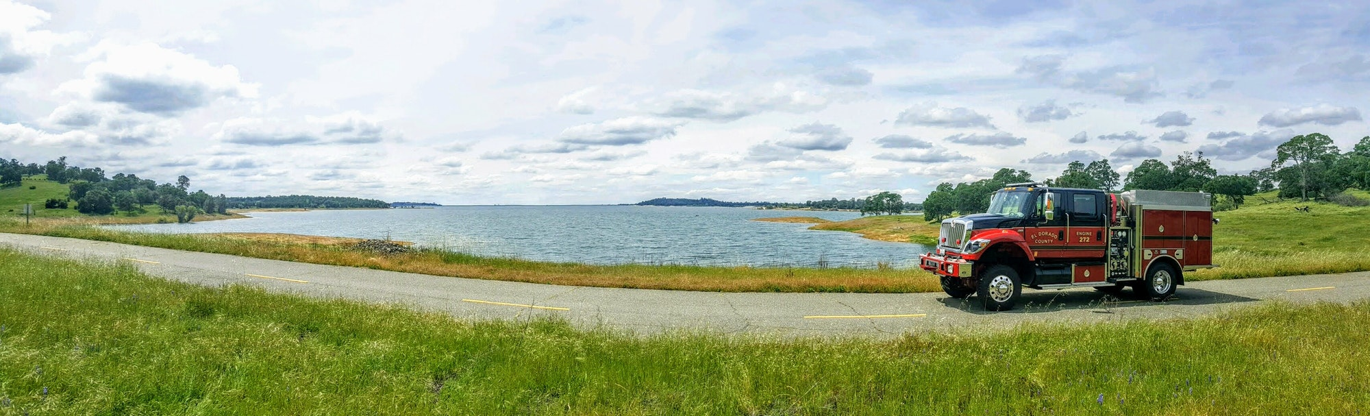 A fire engine along a grass lined road by Folsom Lake, clouds, water, lake, grass, trees, meadow