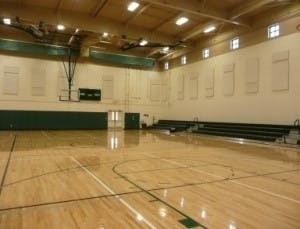 Contains: empty gym from one corner, showing high ceilings, and bleachers on one end of the room.